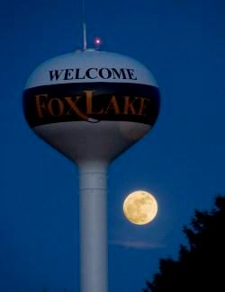 A watertower illuminated by moonlight